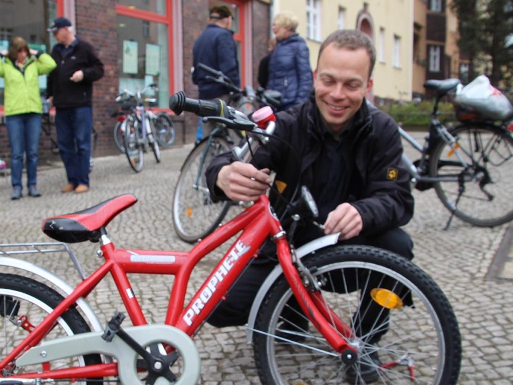 André Kamin befestigt einen Kinderrad Vorderlicht