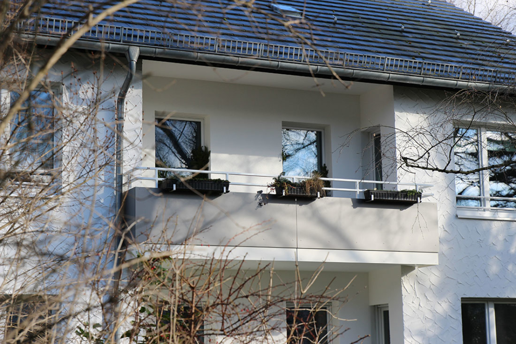 Drei Bügelpaare für Blumenkästen an einem langen Balkon